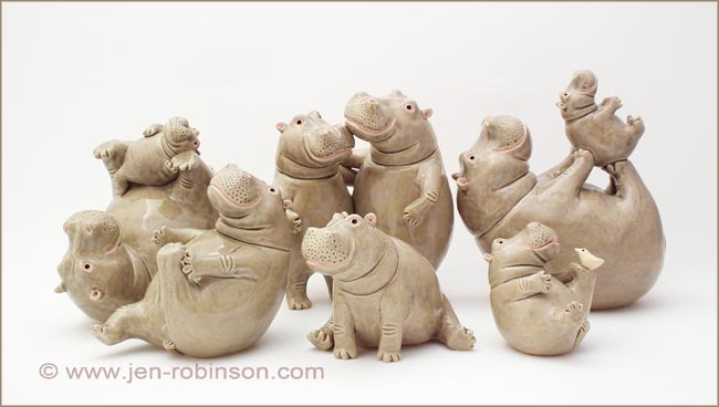 ceramic hippo playing with their babies sculptures