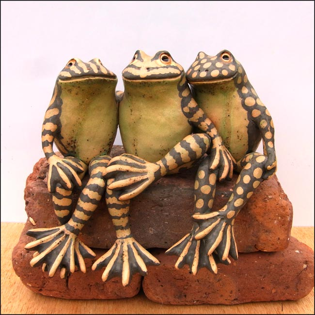 sculpture of three ceramic frogs
